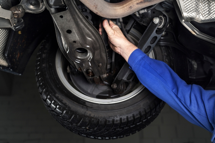 Mechanic is checking the shock absorbers of a modern car